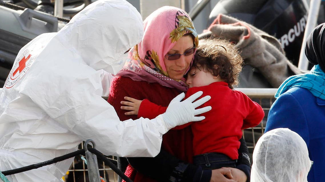 A woman holds her child as they disembark from the Iceland Coast Guard vessel Tyr, at the Messina harbor, Sicily, southern Italy, Wednesday, May 6, 2015. AP