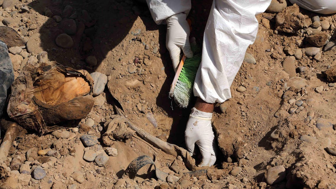 An Iraqi forensic worker excavates human remains in a mass grave, believed to contain the bodies of Iraqi soldiers killed by ISIS militants when they overran. (File: AP)