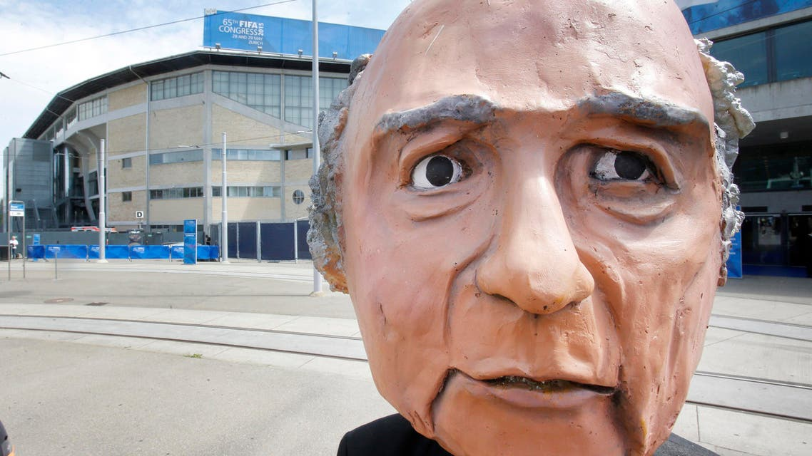 A protester wearing a mask depicting FIFA President Sepp Blatter stands in front of the building where the 65th FIFA congress takes place in Zurich, Switzerland, Friday, May 29, 2015. (AP)