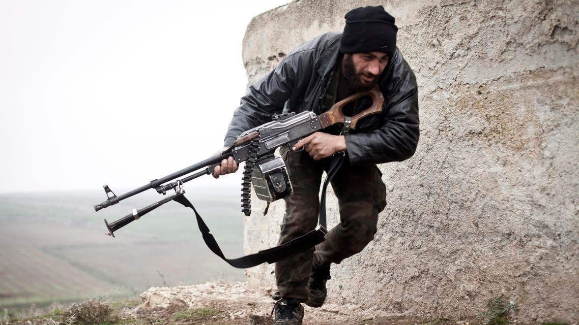 A Free Syrian Army fighter takes cover during fighting with the Syrian Army in Azaz, Syria. (AP)