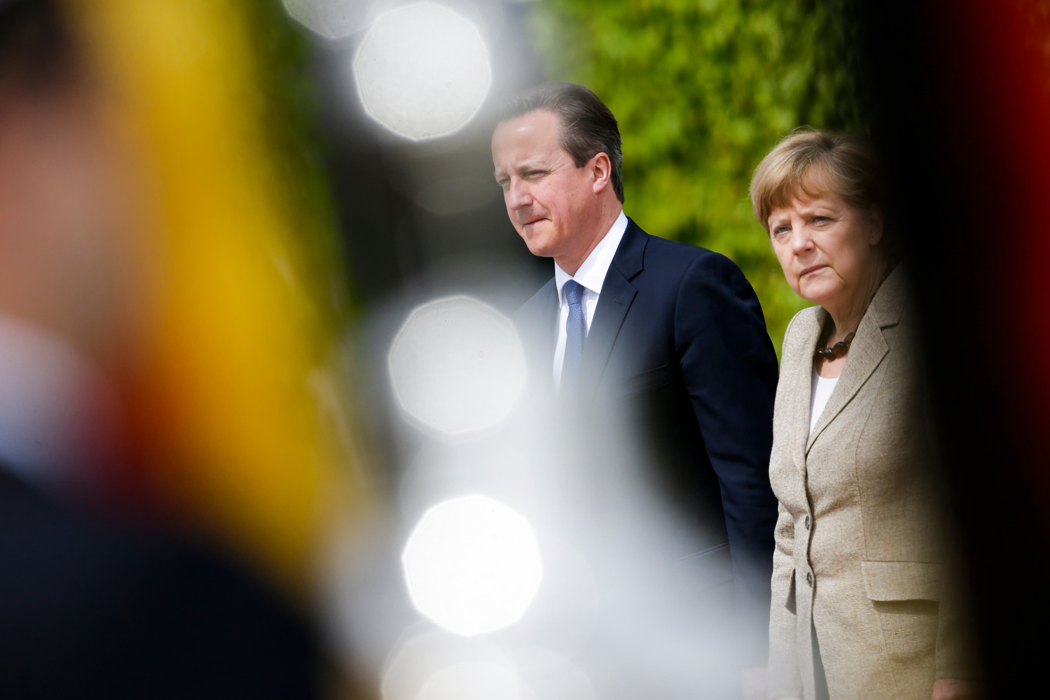 In this photo taken between musicians of the honor guards, German Chancellor Angela Merkel, right, and British Prime Minister David Cameron listen to the national anthems during the welcoming ceremony for a meeting at the chancellery, in Berlin, Germany, Friday, May 29, 2015. (AP Photo/Markus Schreiber)