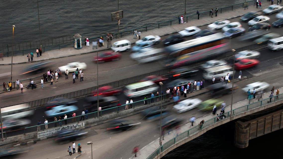 Egyptians wait for the bus on a bridge, in Cairo, Egypt, Monday, Oct. 7, 2013. In a country where the population is around 90 million, bumper-to-bumper traffic has increased mostly in the country's capital. (AP Photo/Hassan Ammar)