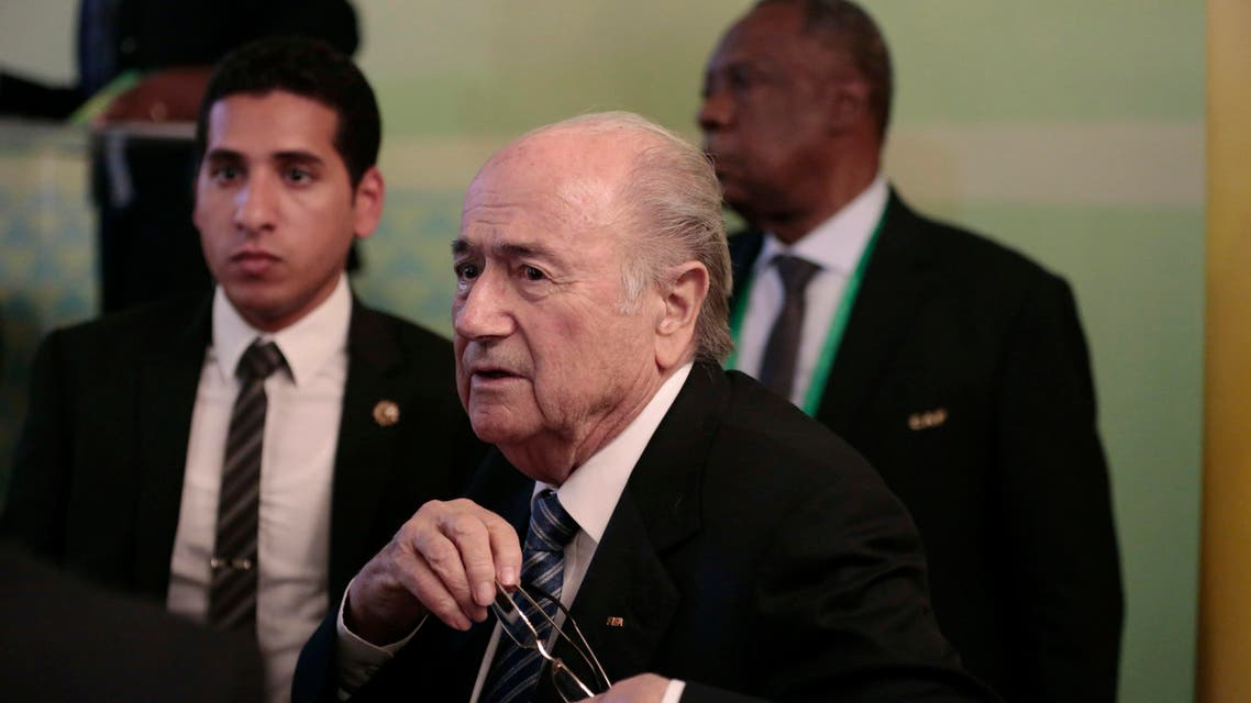 FIFA President Sepp Blatter, center, and Confederation of African Football President Issa Hayatou, back right, leave a press conference in Cairo, Egypt, Tuesday, April 7, 2015. AP