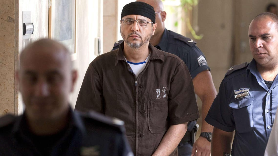 A file picture taken in Jerusalem on June 20, 2012, shows Palestinian Abdallah Barghouti, a leading commander for the Ezzedine al-Qassam Brigades, the armed wing of Hamas in the West Bank, being is escorted by Israeli police into the Magistrate's Court for a hearing. AFP