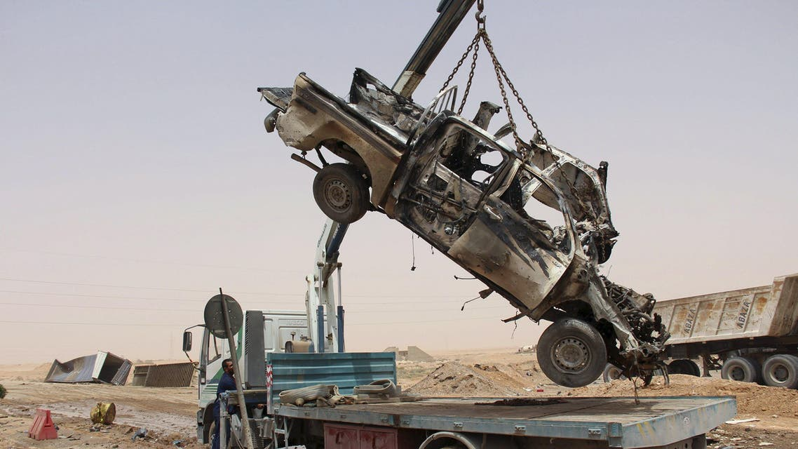 A wreckage of a vehicle is lifted by a crane after a suicide car bomber blew himself at a checkpoint near Mistrata, Libya May 21, 2015.