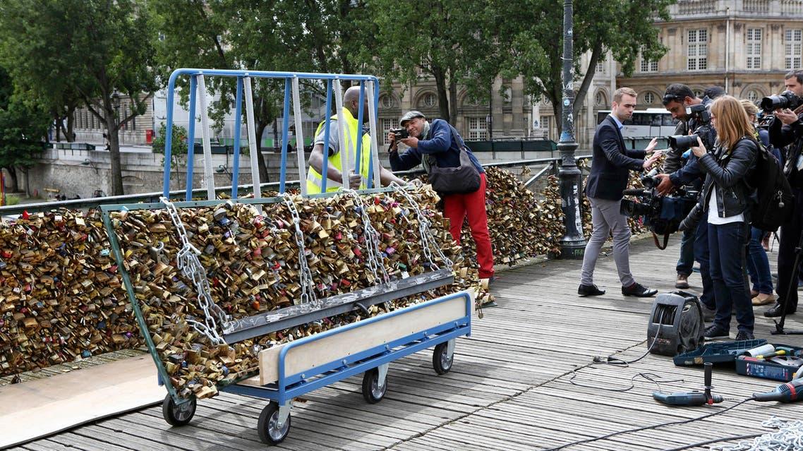 A Paris city employee removes a railing loaded with locks on the famed Pont des Arts bridge in Paris, Monday June 1, 2015. AP