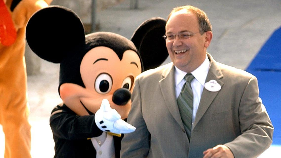 President of Walt Disney Parks and Resorts Jay Rasulo is accompanied by Disney character Mickey Mouse during a topping off ceremony at Hong Kong Disneyland on Thursday, Sept. 23, 2004. Workers used a crane to put a mock turret atop the Sleeping Beauty's castle at Hong Kong Disneyland on Thursday, giving locals their best look yet at the theme park intended to boost tourism revenues when it opens. The main structure of the castle was complete once the trademark blue pointed turret was installed at a ceremony attended by invited guests and journalists who were allowed onto the park site for the first time to view the construction. (AP Photo/Anat Givon)