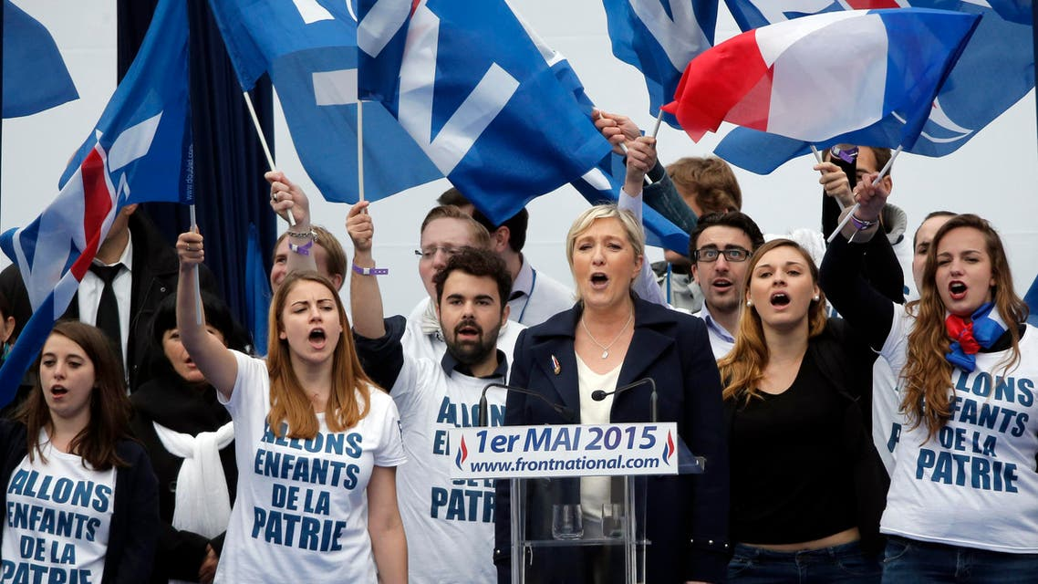 France's far-right National Front president Marine Le Pen, center, surrounded by supporters sing the French National Anthem after her speech at Opera Plaza during the annual May Day march, in Paris, France, Friday, May 1, 2015. France's far-right National Front is holding its annual May Day march, but for the first time the party's founder Jean-Marie Le Pen is not taking a seat at the tribune. (AP Photo/Francois Mori)