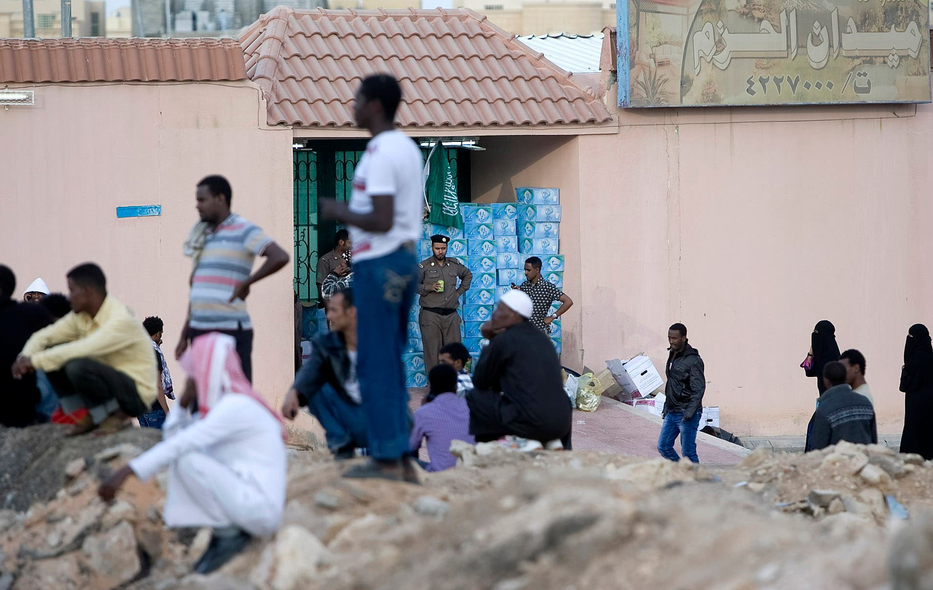 "FILE - In this Wednesday, Nov. 13, 2013 file photo, Saudi security forces watch Ethiopians gather as they wait to be repatriated in Manfouha, southern Riyadh. Saudi Arabia says it has deported ""more than a quarter million"" foreign migrant workers from the kingdom over the past three months. (AP Photo, File)"