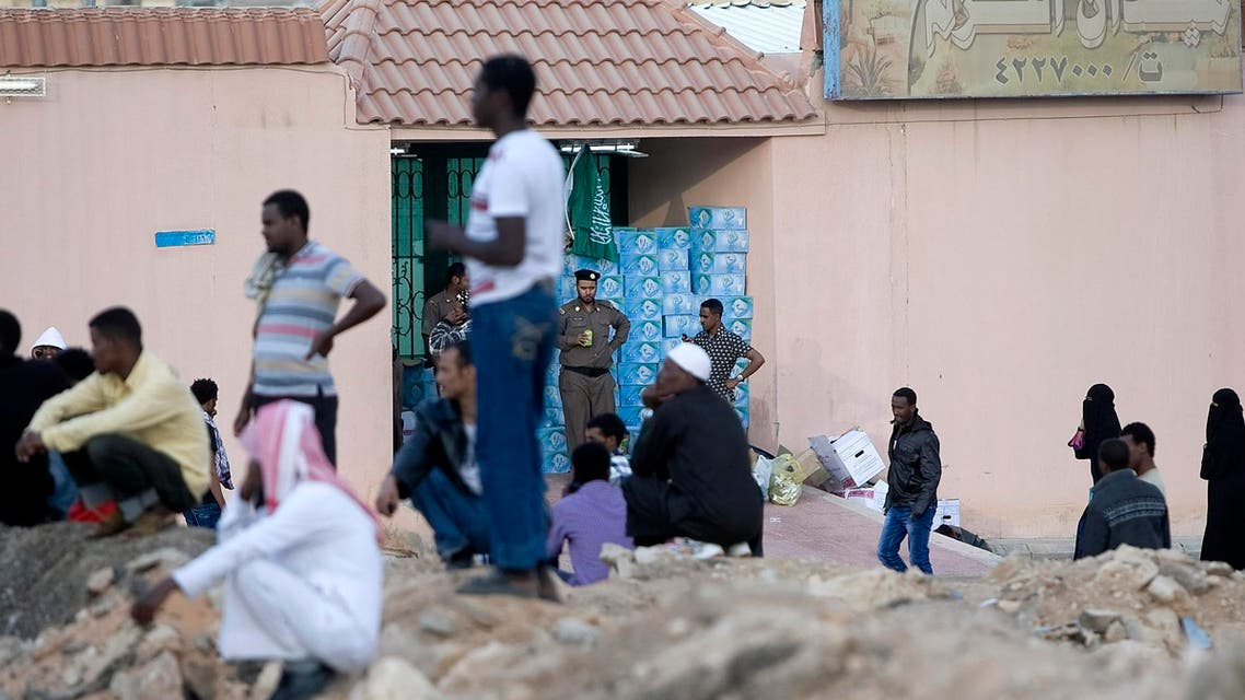 """FILE - In this Wednesday, Nov. 13, 2013 file photo, Saudi security forces watch Ethiopians gather as they wait to be repatriated in Manfouha, southern Riyadh. Saudi Arabia says it has deported """"more than a quarter million"""" foreign migrant workers from the kingdom over the past three months. (AP Photo, File)"""