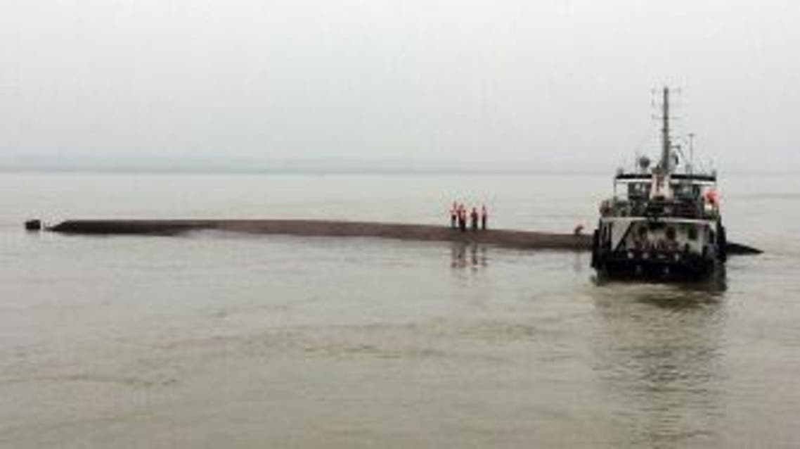 """BEJ3211 - YANGTZI RIVER, Hubei, CHINA : A Chinese rescue boat is seen alongside a capsized passenger ship carrying more than 450 people which sunk in the Yangtze river, triggering a rescue effort hampered by strong winds and heavy rain off Jianli in China's Hubei province on June 2, 2015. The ship named Dongfangzhixing, or """"Eastern Star"""", was headed from the eastern city of Nanjing to the southwestern city of Chongqing when it sank in the Jianli section of the river. CHINA OUT AFP PHOTO"""