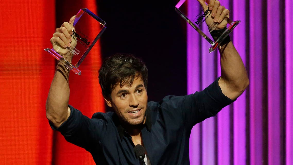 Singer Enrique Iglesias raises the Latin Pop Album of the Year and the Latin Pop Songs Artist of the Year, Solo awards during the Latin Billboard Awards Thursday, April 30, 2015 in Coral Gables, Fla. (AP Photo/Lynne Sladky)