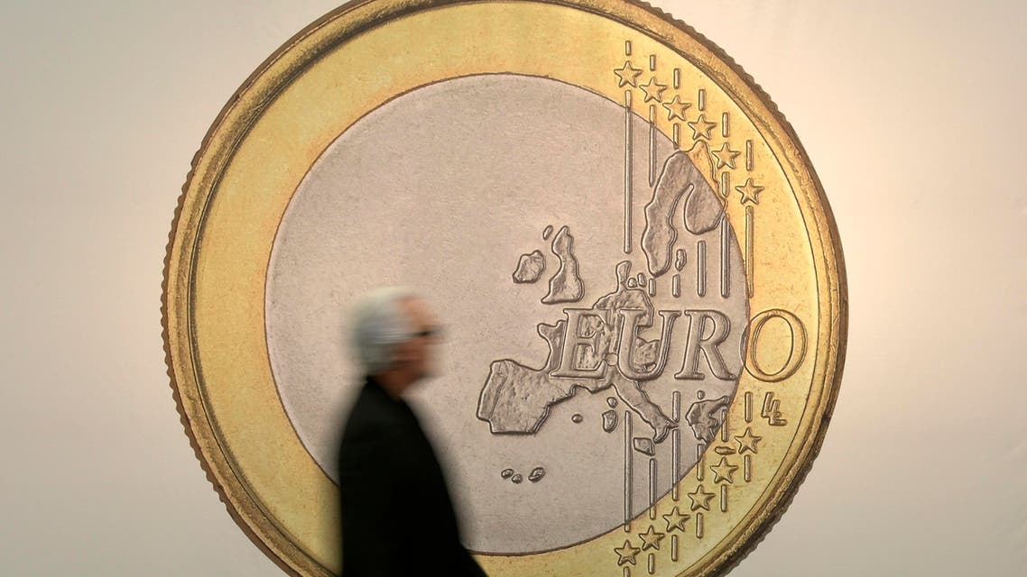 """A man passes the artwork """"Euro"""" by artist group Superflex at the art fair in Cologne, Germany, Thursday, April 16, 2015. (AP Photo/Martin Meissner)"""