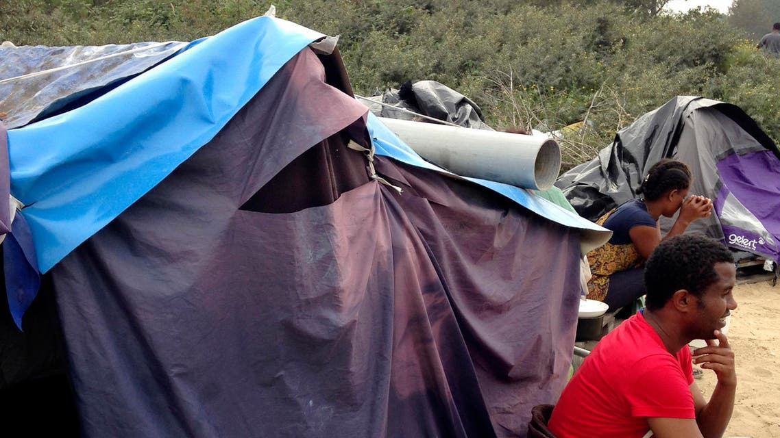 In this photo taken Sunday, Sept. 7, 2014, migrants sit by a tent at a makeshift camp in Calais, northern France. Migrants huddle in shanty-towns in Calais, gazing out at a tantalizingly narrow stretch of water toward Britain - the land they see as their Eldorado. They are pouring into the French port city at an ever-faster pace, overwhelming police with aggressive new tactics in their bid to cross the English Channel. (AP Photo/Elaine Ganley)