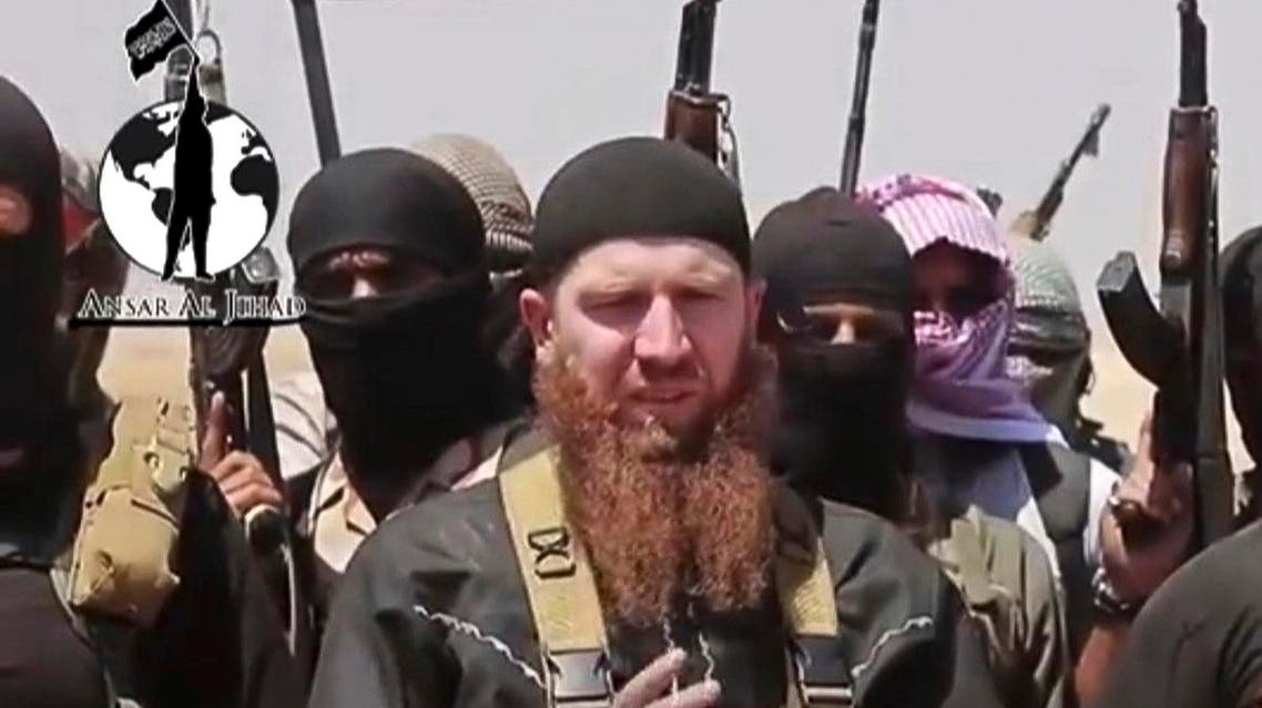 This image made from undated video posted during the weekend of June 28, 2014 on a social media account frequently used for communications by the Islamic State, which has been verified and is consistent with other AP reporting, shows Omar al-Shishani standing next to the group's spokesman among a group of fighters as they declare the elimination of the border between Iraq and Syria. In the Pankisi, the mountainous region of northeastern Georgia where he was born in 1986, the ginger-bearded commander is a hero and a role model. Following the path he blazed, as many as 200 of his young countrymen have left their villages. (Militant social media account via AP)