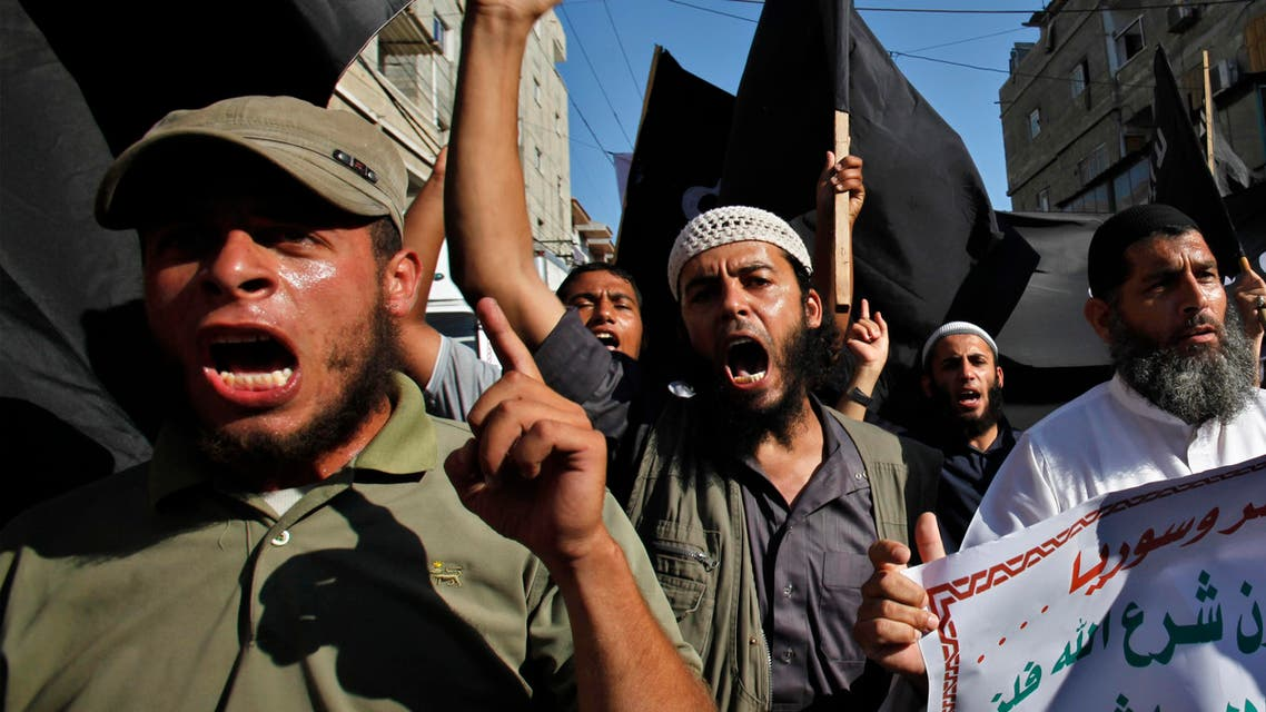 """FILE - In this Thursday, Aug. 22, 2013 file photo, Palestinian members from Youth Salafists group chant slogans while waving their black flags during a protest against the Egyptian and Syria regimes in Rafah Refugee Camp, southern Gaza Strip. Arabic on poster reads """"Criminals and murderers"""". A leader of one of Gaza's secretive salafist militant groups says the al-Qaida-inspired movement now has several thousand armed fighters in the seaside strip, posing a formidable threat to both Israel and the area's Hamas rulers. (AP Photo/Adel Hana, File)"""