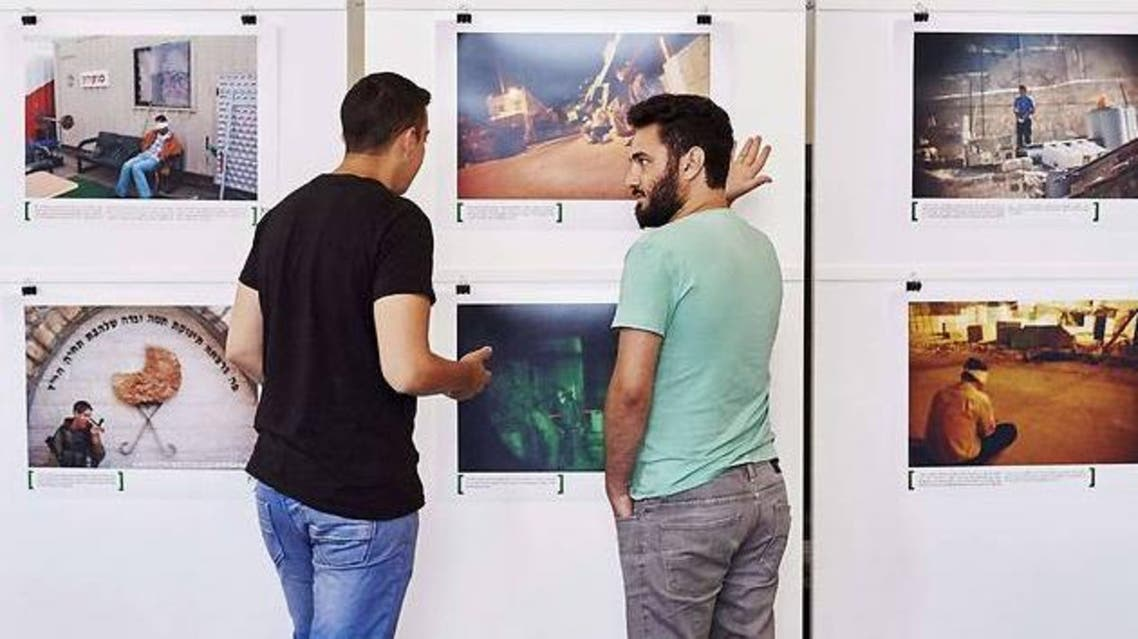 """Alon Sahar (L) and Shay Davidovich, both former Israeli army soldiers, discuss in front of photographs at an exhibition of the Israeli NGO """"Breaking the Silence"""" at the Kulturhaus Helferei in Zurich (Photo: AFP)"""