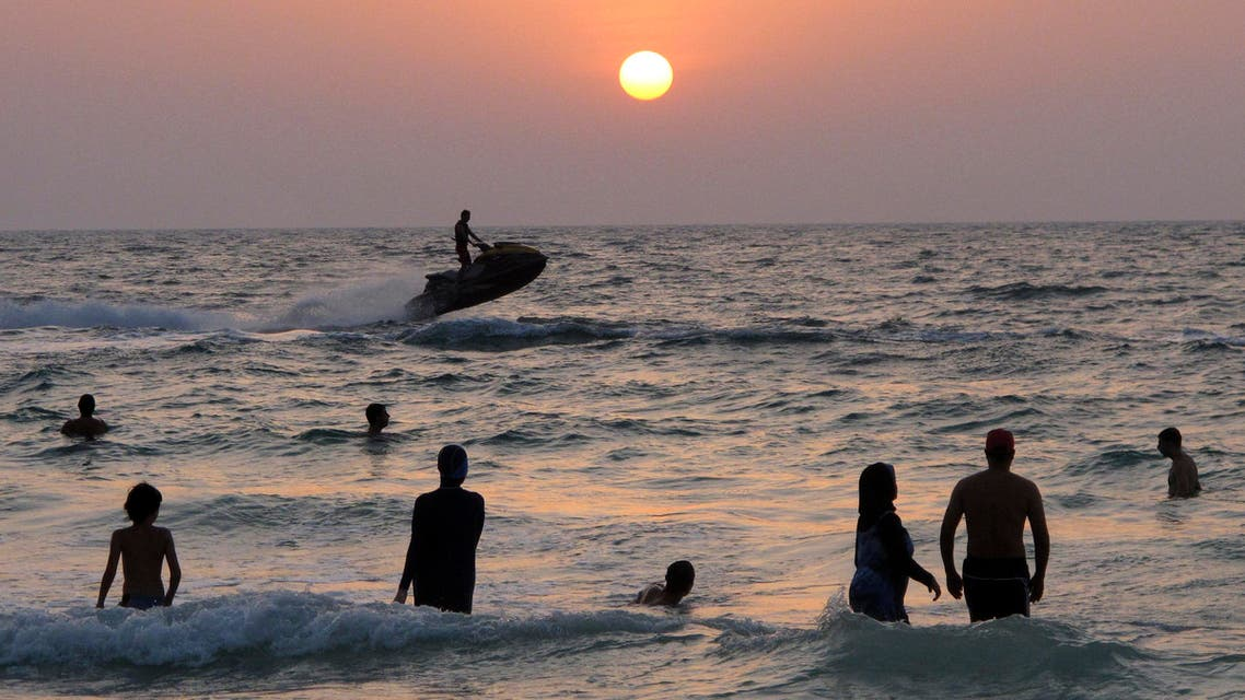 People enjoy a sunset swim at a public beach in Dubai, United Arab Emirates, Thursday, Sept. 6, 2012. (AP Photo/Hassan Ammar)