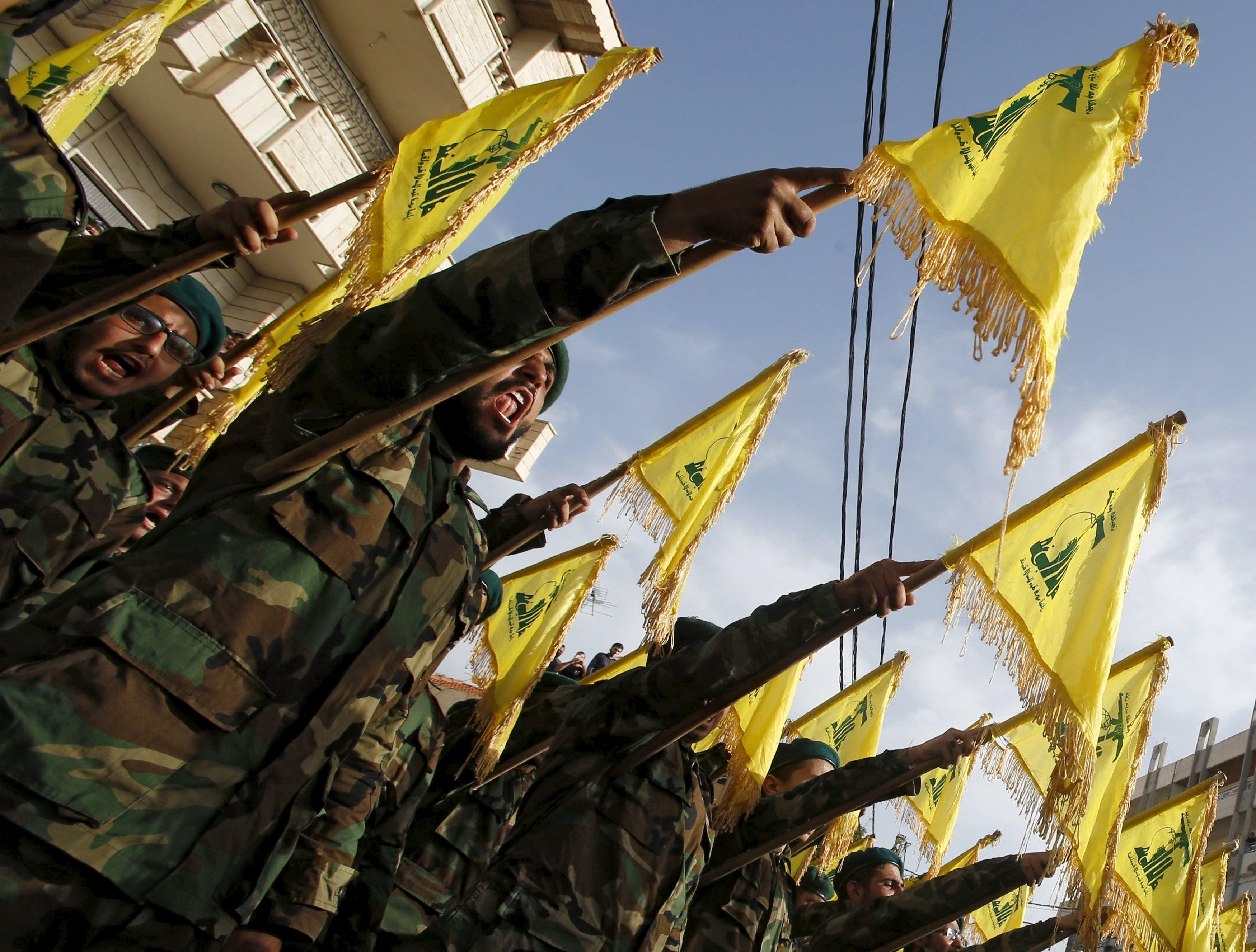Lebanon's Hezbollah members carry Hezbollah flags during the funeral of their fellow fighter Adnan Siblini, who was killed while fighting against insurgents in the Qalamoun region, in al-Ghaziyeh village, southern Lebanon May 26, 2015. Hezbollah is fighting across all of Syria alongside the army of Syria's President Bashar al-Assad and is willing to increase its presence there when needed, the leader of the Lebanese Shi'ite movement said on Sunday. REUTERS/Ali Hashisho