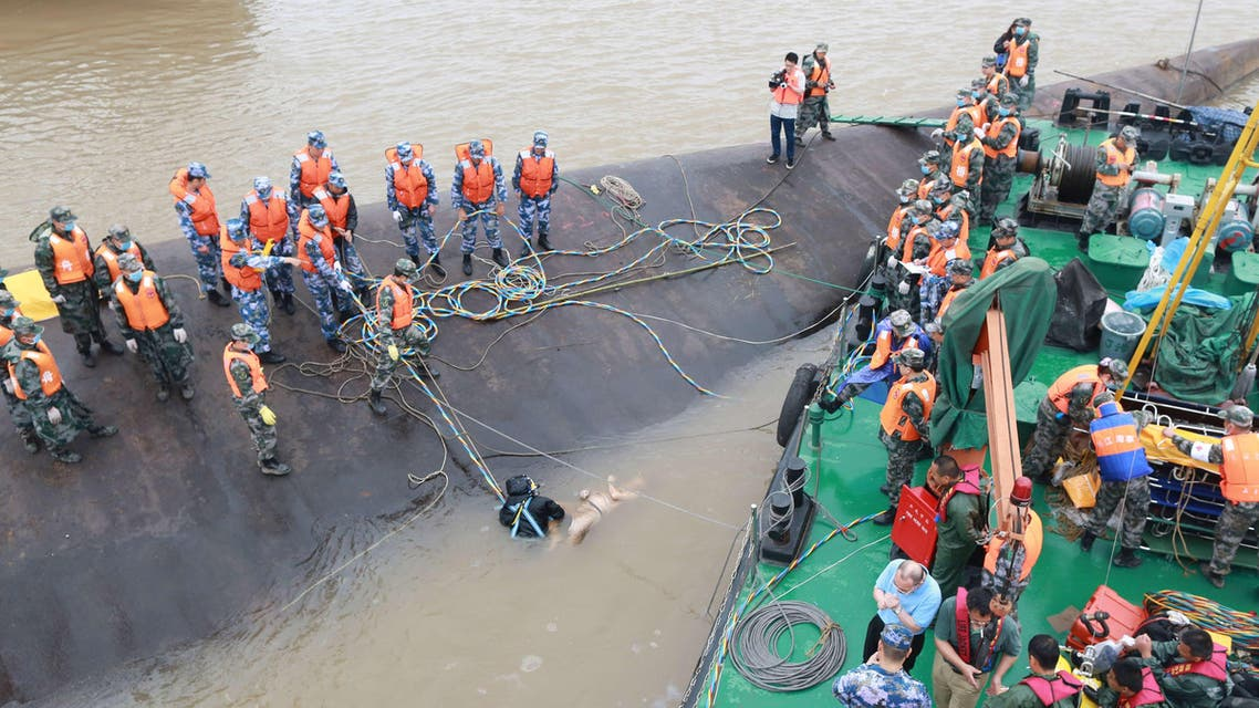"""Rescue personnel and divers retrieve the body (C) of a passenger who was travelling on the capsized passenger ship Dongfangzhixing or """"Eastern Star"""" in the Yangtze river at Jianli in China's Hubei province on June 3, 2015. AFP"""