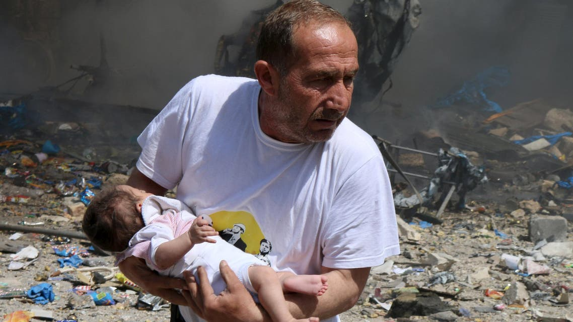 A man holds a baby that survived what activists said was a site hit by a barrel bomb dropped by forces loyal to Syrian President Bashar al-Assad at the old city of Aleppo, (Reuters)