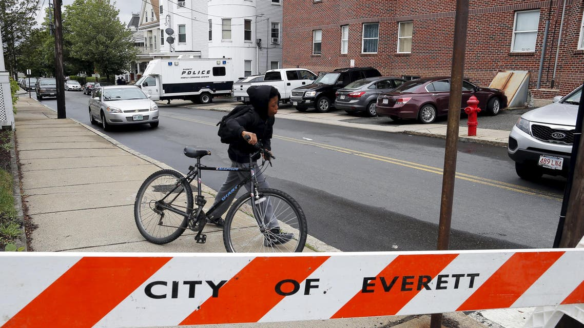 A local youth wheels his bicycle past law enforcement officials are gathered on a residential street in Everett, Massachusetts June 2, 2015. (Reuters)