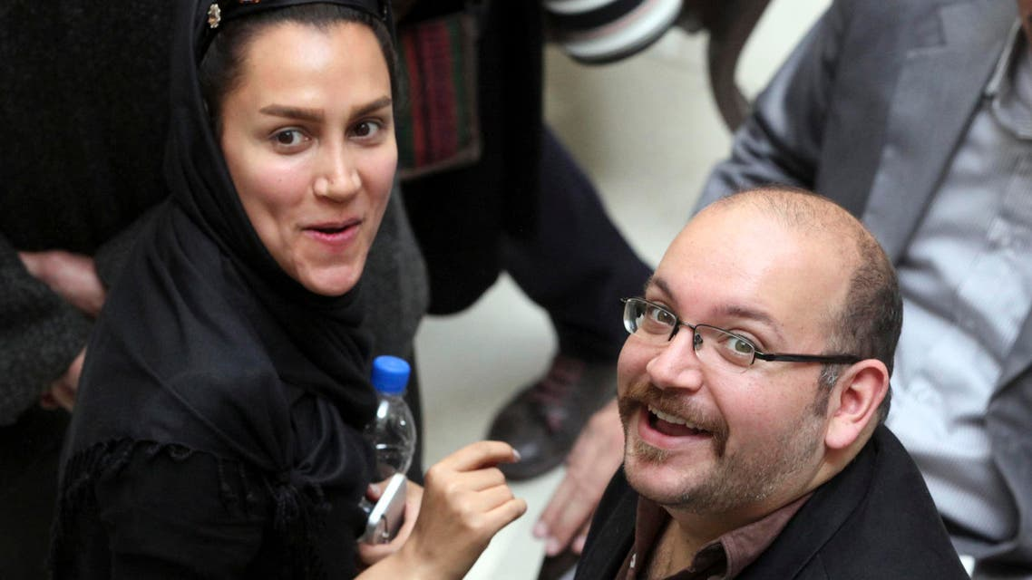 In this April 11, 2013 file photo, Jason Rezaian, right, an Iranian-American correspondent for the Washington Post, and his wife Yeganeh Salehi, an Iranian correspondent for the Abu Dhabi-based daily newspaper, The National, smile as they attend a presidential campaign of President Hassan Rouhani in Tehran, Iran. (AP)