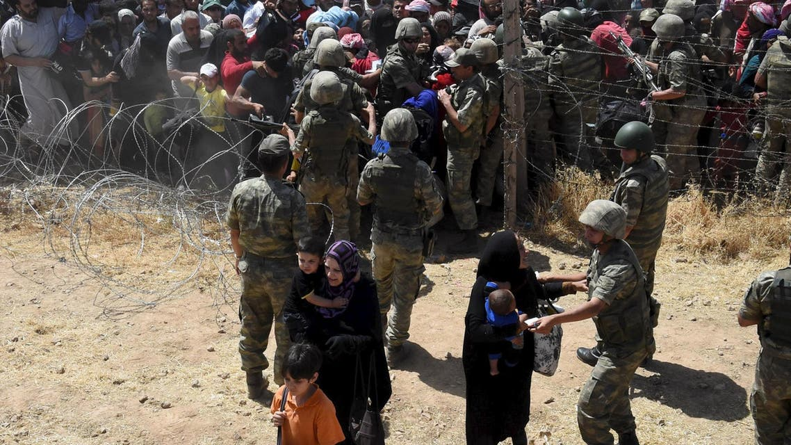 Turkish soldiers help Syrian refugees as they cross into Turkey on the Turkish-Syrian border, near the southeastern town of Akcakale in Sanliurfa province, Turkey. (Reuters)