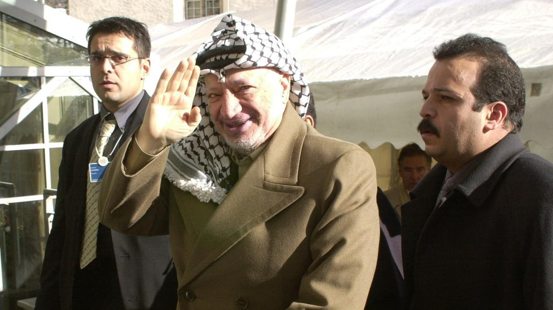 Palestinian leader Yasser Arafat arrives at his Davos hotel accompanied by security agents on Sunday Jan. 28, 2001. Arafat will address the World Economic Forum in Davos together with Israel's Minister of Regional Cooperation Shimon Peres later in the day. (File Photo; AP)