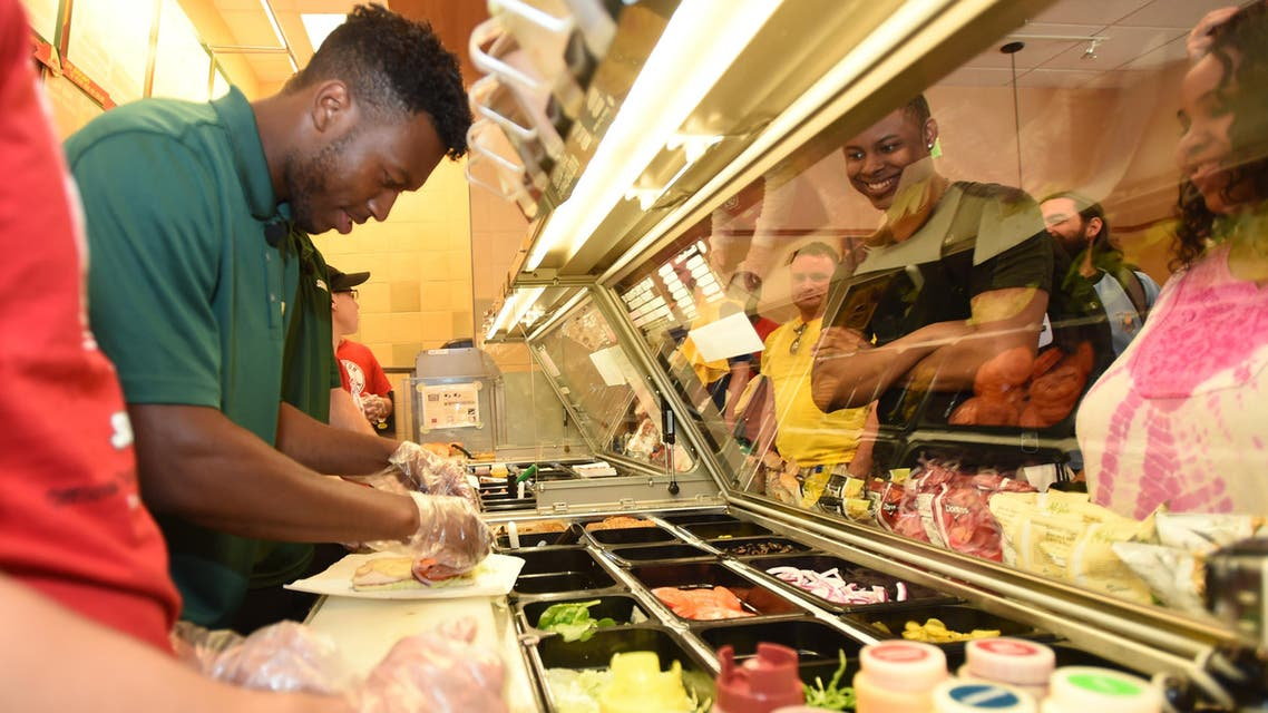 Liverpool FC Striker Daniel Sturridge prepares a sandwich for a fan at a Subway Restaurant on Friday, July 25, 2014 in Boston. (File Photo; AP)