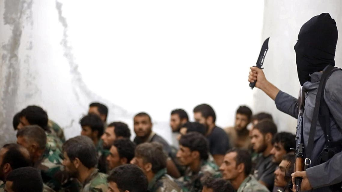 A fighter from ISIS, armed with a knife and an automatic weapon, next to captured Syrian army soldiers and officers. (File Photo: AP)