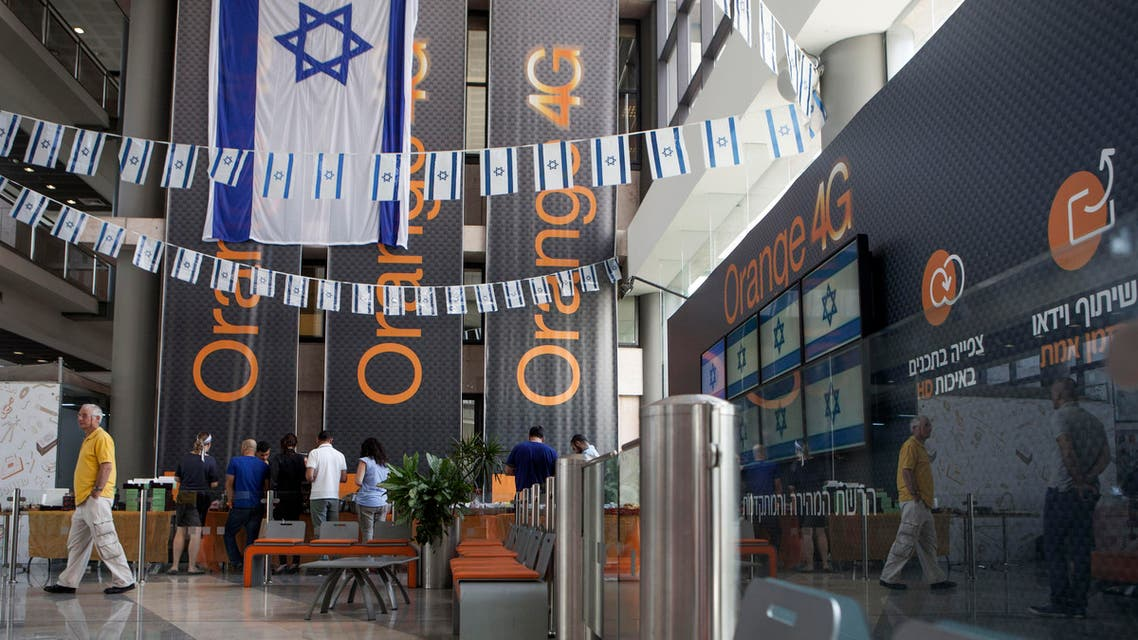 """Israeli flags are seen inside the """"Partner Orange"""" Communications Company offices in the city of Rosh Haain, Israel, Thursday, June 4, 2015. An Israeli Cabinet minister has called on the French president to fire the chief executive of French telecom giant Orange. Culture Minister Miri Regev issued her appeal on Thursday, a day after Orange's CEO announced in Cairo that he would like to sever his company's ties to Israel as soon as possible. (AP Photo/Dan Balilty)"""