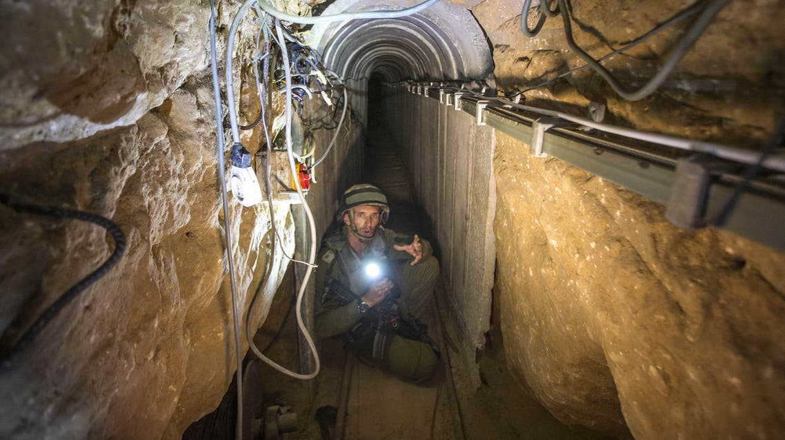 """An Israeli army officer gives journalists a tour, Friday, July 25, 2014, of a tunnel allegedly used by Palestinian militants for cross-border attacks, at the Israel-Gaza Border. A network of tunnels Palestinian militants have dug from Gaza to Israel, dubbed """"lower Gaza"""" by the Israeli military, is taking center stage in the latest war between Hamas and Israel. (AP Photo/Jack Guez, Pool)"""