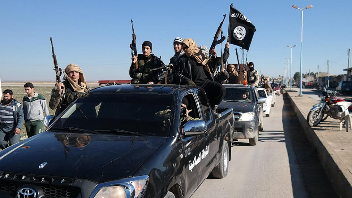 Islamic State militants pass by a convoy in Tel Abyad town, northeast Syria. AP