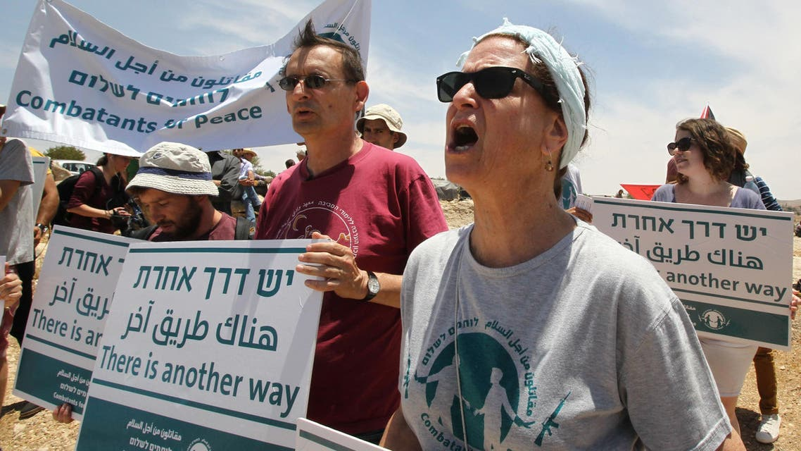 Palestinians, foreigners and Israeli peace activists hold banners and shout slogans as they demonstrate against the demolition of the southern West Bank Palestinian village of Susya and in support of the citizens in the southern area near the town of Hebron on June 5, 2015. (AFP)