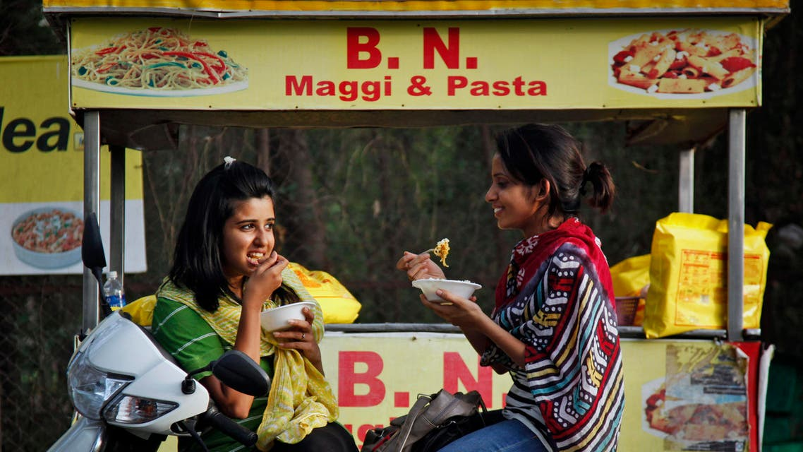 "Indian girls eat noodles at a roadside stall in Ahmadabad, India, Thursday, June 4, 2015. Indian shopkeepers withdrew a popular brand of Nestle instant noodles ""Maggi"" from their shelves on Wednesday, June 3, 2015, after tests revealed the snack contained unsafe levels of lead. (AP Photo/Ajit Solanki)"