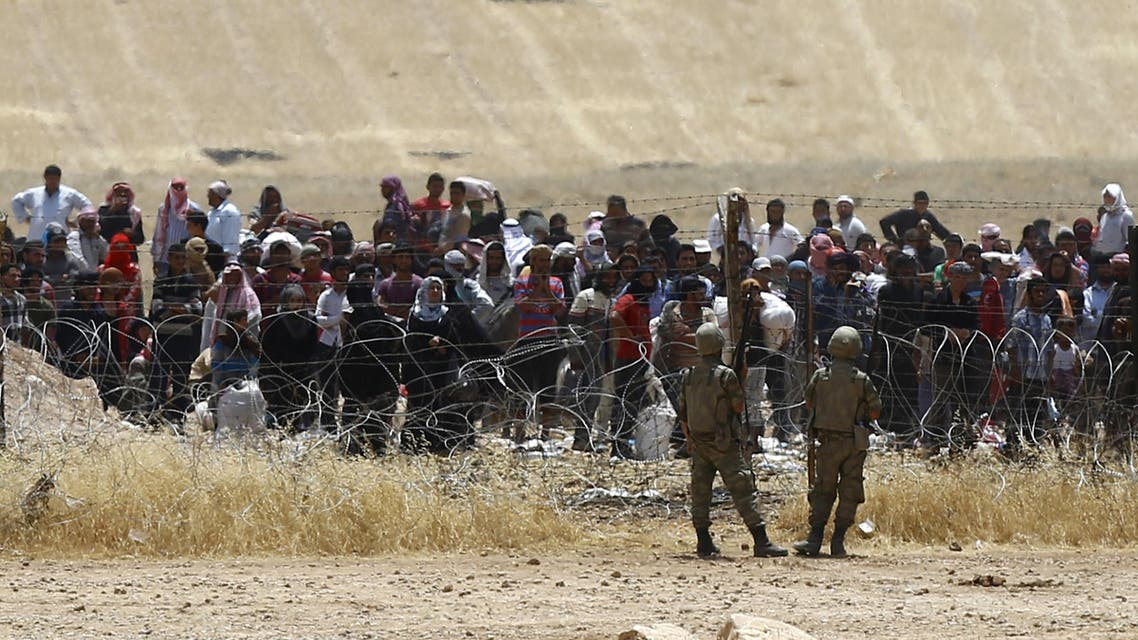 Turkish soldiers stand guard as Syrian refugees wait behind the border fences to cross into Turkey on the Turkish-Syrian border, near the southeastern town of Akcakale in Sanliurfa province, Turkey, June 5, 2015. Reuters