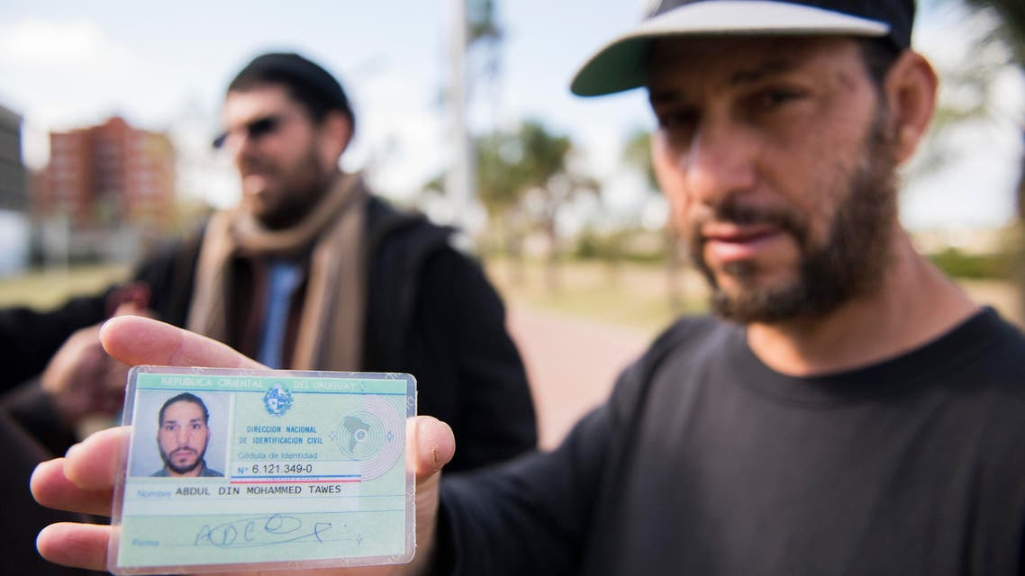 freed Guantanamo Bay detainee Adel bin Muhammad El Ouerghi, of Tunisia shows his Uruguayan identification card in front of the U.S. embassy in Montevideo, Uruguay. AP