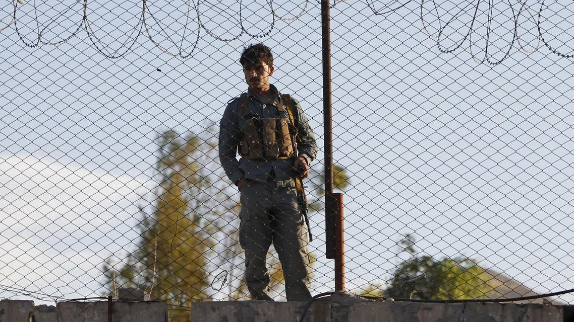 An Afghan policeman keeps watch after a suicide attack on a police headquarters in Jalalabad, Afghanistan June 1,  2015 (Reuters)