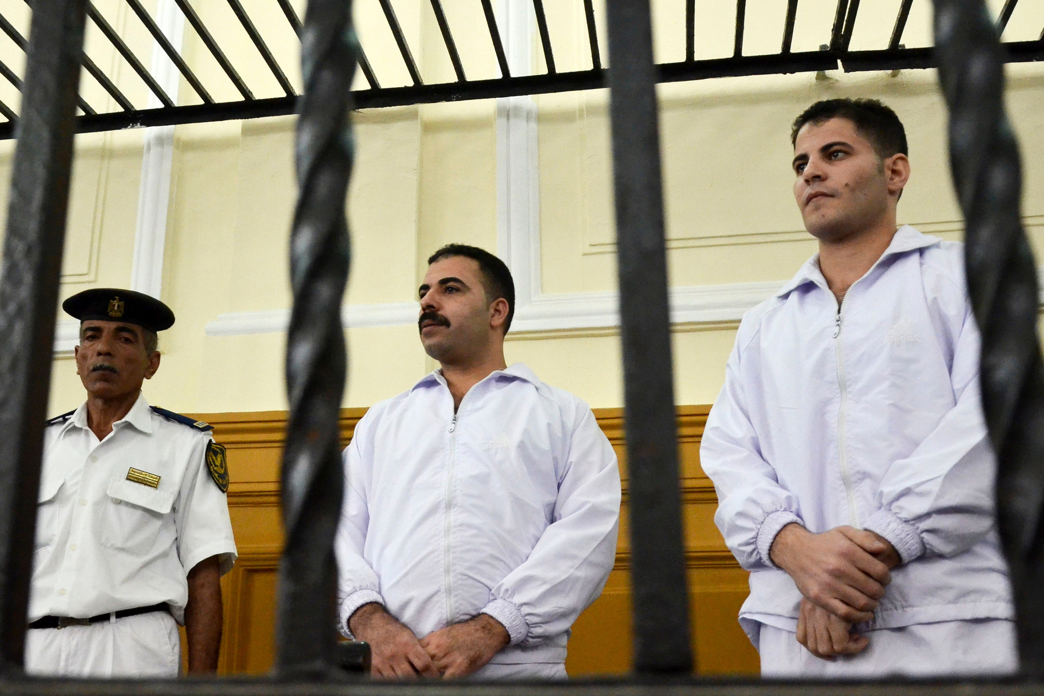 Policemen Awad Ismail, center, and Amin Mahmoud Salah, right, defendants in the beating death of Khaled Said, stand trial in a courtroom in Alexandria, Egypt, Saturday, Sept. 24, 2011. (AP)