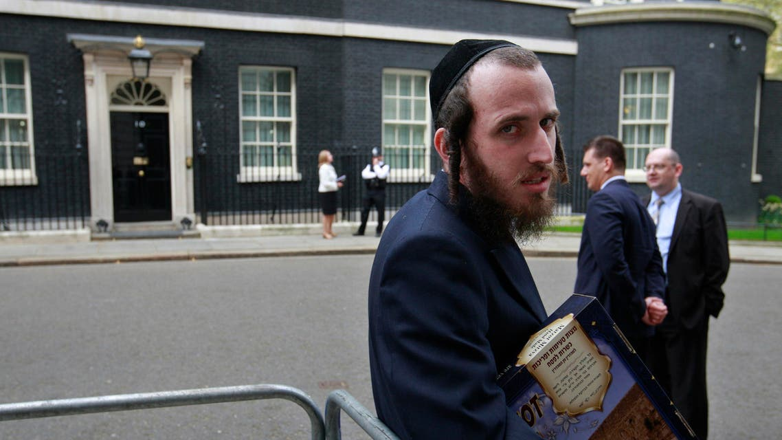 A ultra Orthodox Jewish man, name not given, from the Polish Orthodox Jewish community in London, holds Matzoth bread, in order to give it as a present for the Passover holiday, to Poland's Prime Minister Donald Tusk, not seen, visiting Britain's Prime Minister David Cameron at his official residence at 10 Downing Street in central London, prior to their meeting, Monday April 18, 2011. All leavened food, such as bread, is forbidden to Jews during the week-long Passover holiday commemorating the Israelites' departure from Egypt. (AP Photo/Lefteris Pitarakis)