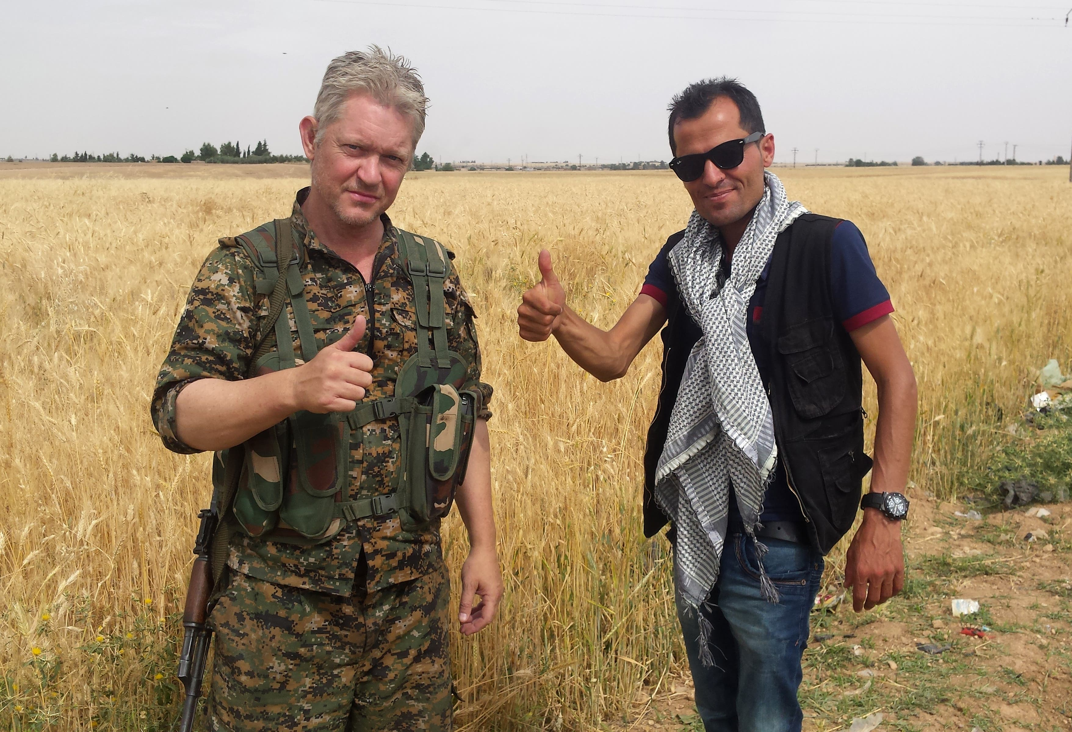Michael Enright, left, a British actor who has had minor roles in Hollywood films, gives a thumbs up with Kurdish journalist Mohammed Hassan, right, as he holds his AK-47 and wears the Kurdish fighters military uniform. (AP)