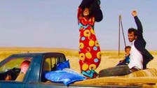 Women escaping ISIS victoriously remove black clothing