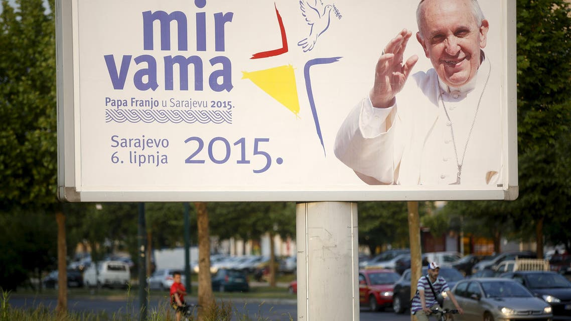People ride bicycles past a billboard with an image of Pope Francis in Sarajevo. (Reuters)
