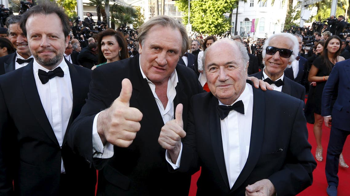 """Actor Gerard Depardieu (C), FIFA President Sepp Blatter (R) and director Frederic Auburtin pose on the red carpet for the screening of the film """"United Passions"""" at the 67th Cannes Film Festival in Cannes, in this May 18, 2014. (File Photo; Reuters)"""