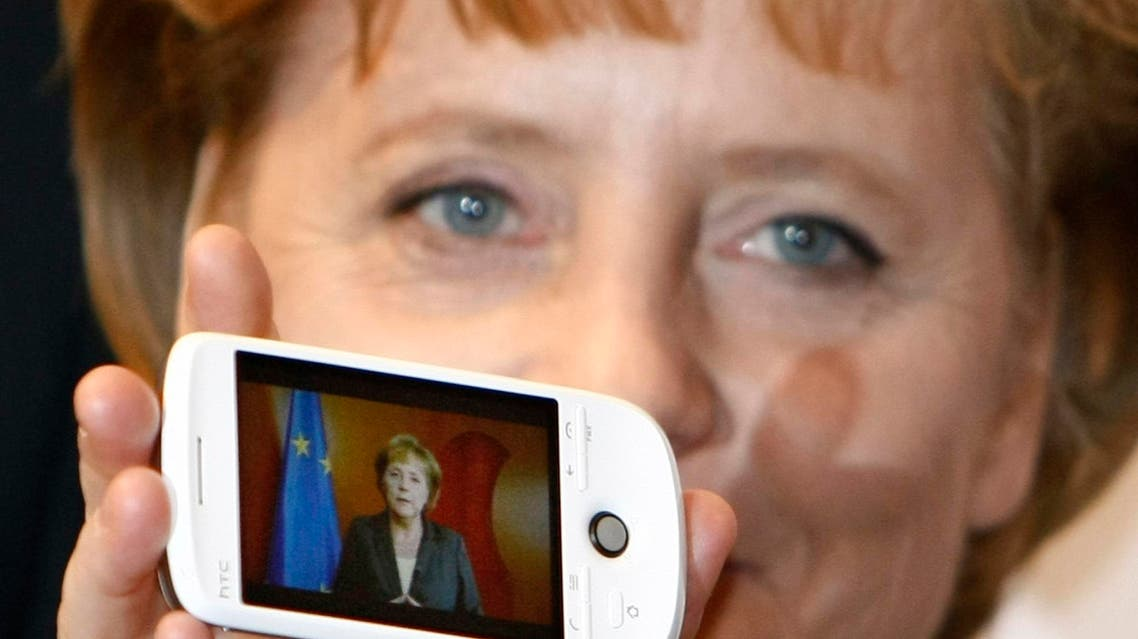 German Chancellor Angela Merkel holds a cell phone with a photo of her on the screen during her opening walk at the CeBIT in Hanover, northern Germany, on Tuesday, March 3, 2009.
