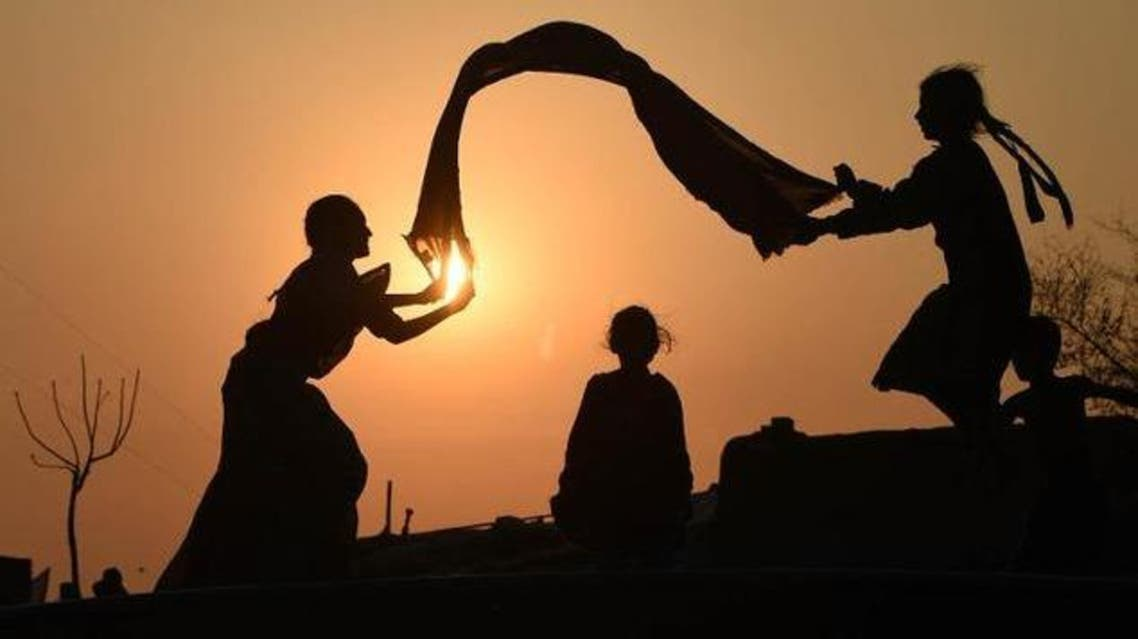Pakistani girls are silhouetted as they play at a slum area of Lahore on March 4, 2015. In Pakistan's conservative patriarchal society daughters are often considered a burde