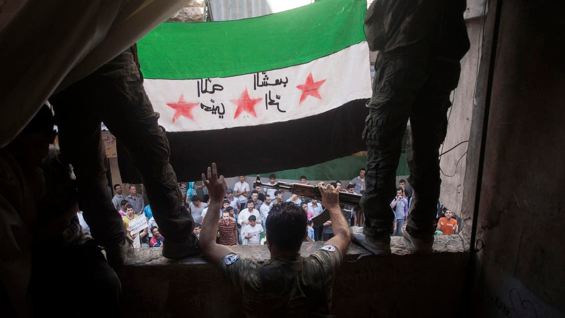 In this Friday, Sept. 21, 2012 file photo, Free Syrian Army rebels hold a revolutionary flag during a demonstration in the Bustan al-Qasr neighborhood of Aleppo, Syria. (File photo: AP)