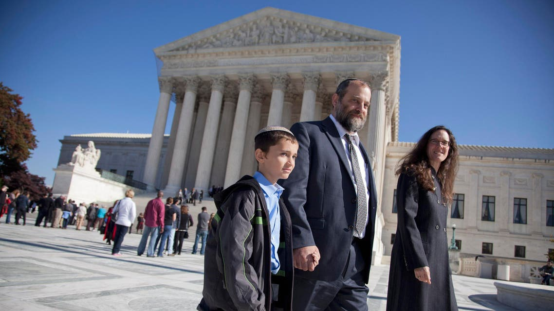 Ari Zivotofsky, center, walks with his nine-year-old son, Menachem, outside the Supreme Court in Washington, Monday, Nov. 7, 2011. AP
