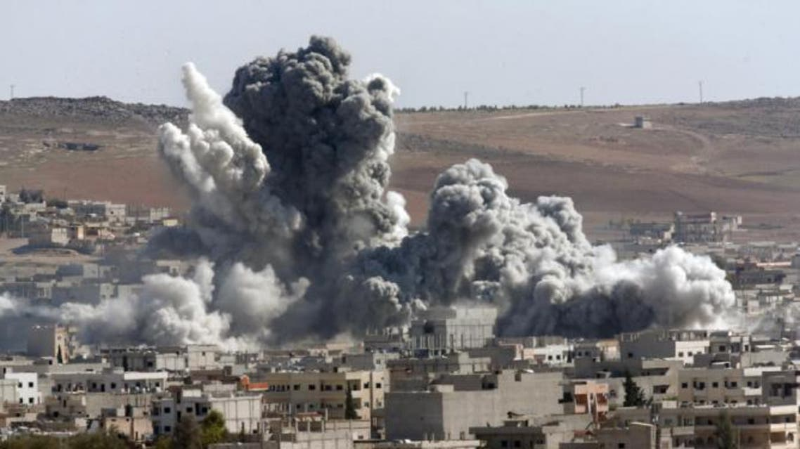 Thick smoke from an airstrike by the US-led coalition rises in Kobani, Syria, as seen from a hilltop on the outskirts of Suruc, at the Turkey-Syria border, Wednesday, Oct. 22, 2014. AP